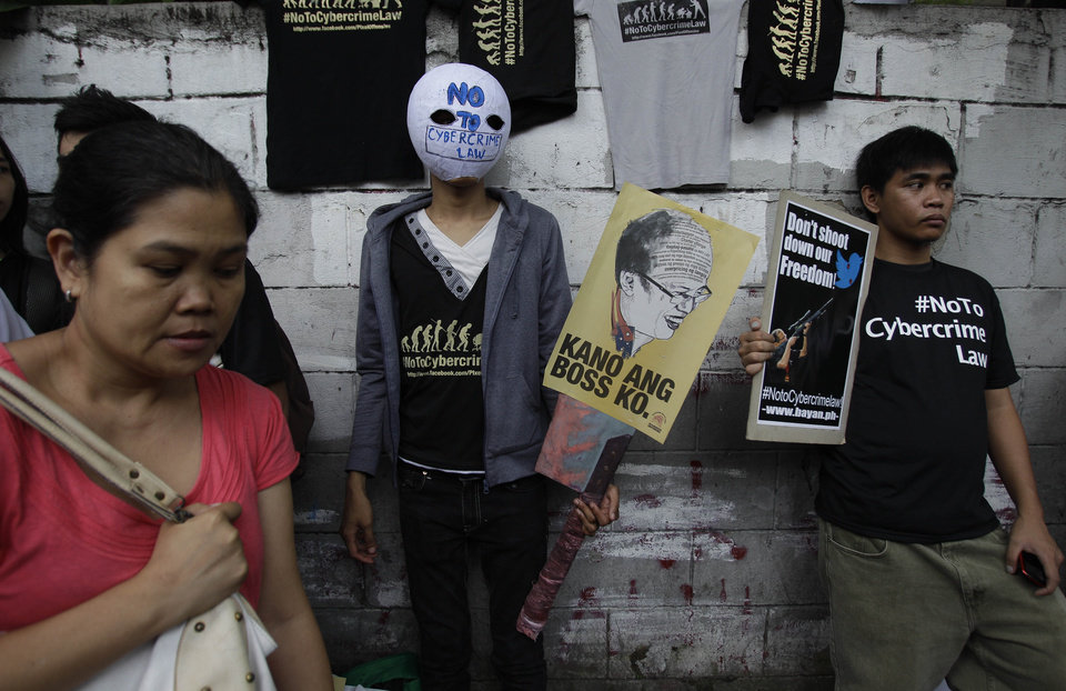 A protester wears a mask bearing a slogan as he joins a rally against the anti-cybercrime law in front of the Supreme Court in Manila, Philippines, Tuesday Oct. 9, 2012. The Philippine Supreme Court on Tuesday suspended implementation of the country's anti-cybercrime law while it decides whether certain provisions violate civil liberties. The law aims to combat Internet crimes such as hacking, identity theft, spamming, cybersex and online child pornography. (AP Photo/Aaron Favila)
