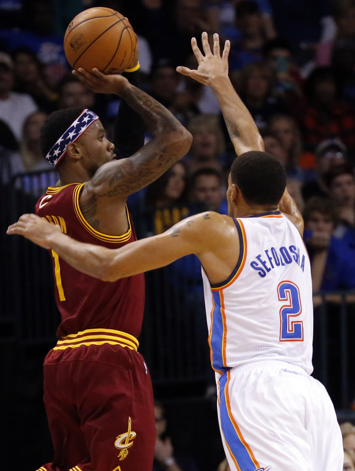 Photo - Oklahoma City's Thabo Sefolosha (2) defends against Cleveland's Daniel Gibson (1) during the NBA basketball game between the Oklahoma City Thunder and the Cleveland Cavaliers at the Chesapeake Energy Arena, Sunday, Nov. 11, 2012. Photo by Sarah Phipps, The Oklahoman