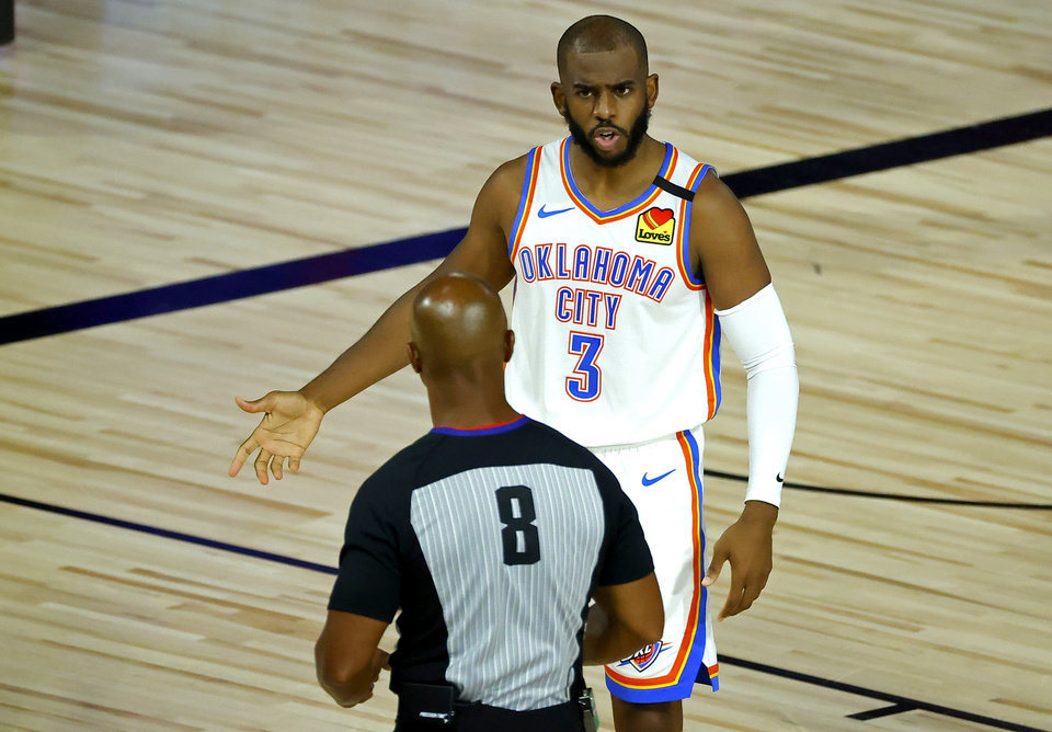 Photo - OKC's Chris Paul discusses a call with referee Marc Davis on Wednesday at HP Field House at ESPN Wide World Of Sports Complex in Lake Buena Vista, Florida. Paul led the Thunder to a 105-86 rout of the Los Angeles Lakers. [Kevin C. Cox/Pool Photo-USA TODAY Sports]