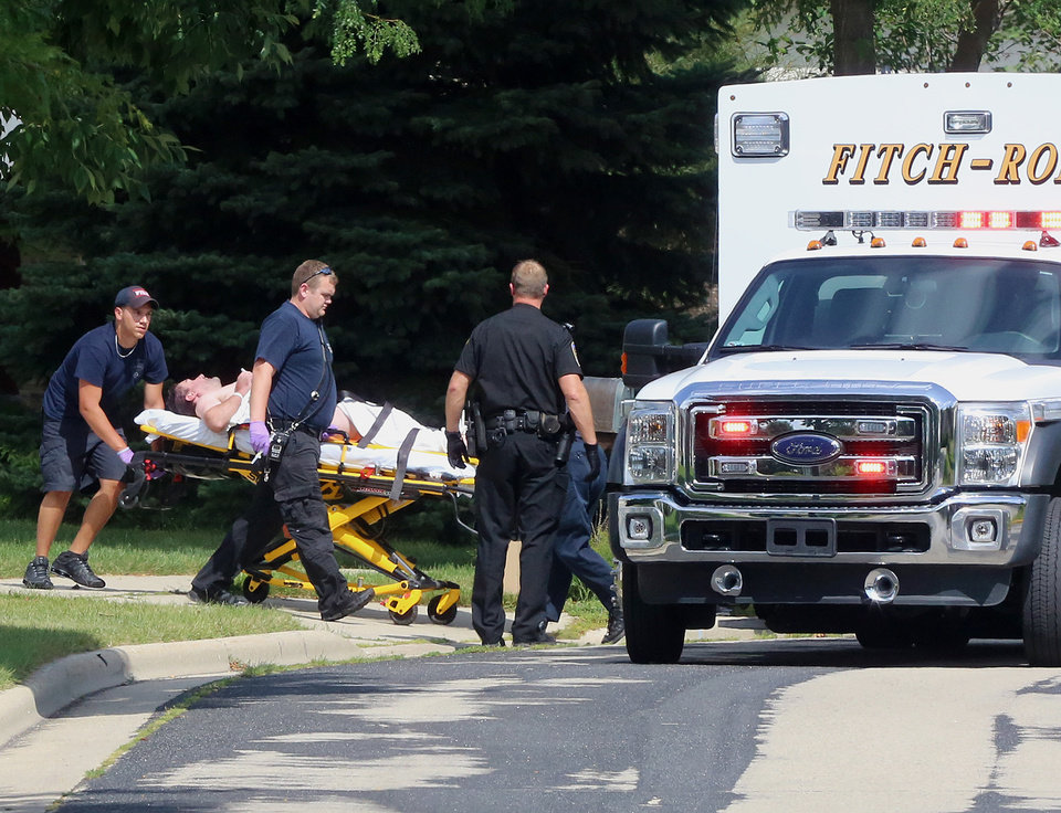 Photo - In this Aug. 22, 2014 photo emergency personnel transport Andy Steele, a recently retired Dane County sheriff's deputy, from his hom in Fitchburg, Wis. Authorities said Steele, 39, has been arrested in the fatal shooting of his wife, Ashlee Steele, 39, and sister-in-law, Kacee Tollesfsbol, 38, who were found shot dead in the Steele home. Charges are expected early this week, according to police. (AP Photo/Wisconsin State Journal, John Hart)