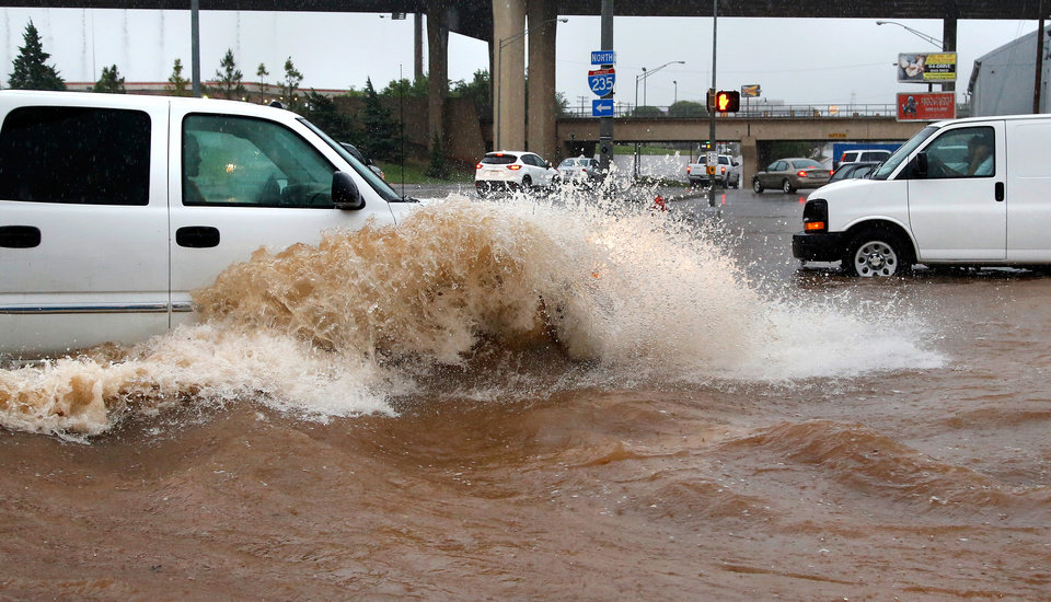 Photo - A truck creates a wave as it forces its way through high water at NW 23 and Broadway. Brief periods of heavy rain caused road flooding and created hazardous driving conditions around 7 pm Saturday, May 23, 2015.  Oklahoma City police used their vehicles to barricade all directions of traffic at NW 23 and Broadway, preventing vehicles from driving into high and rushing water. Photo by Jim Beckel, The Oklahoman.