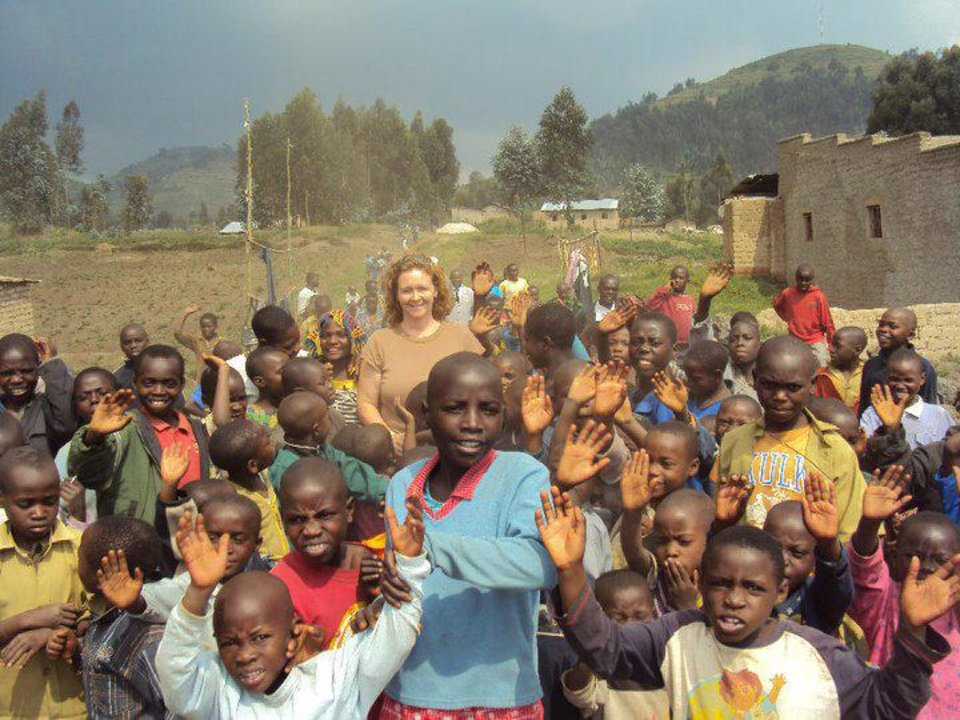 Photo - Apples for Africa founder Sharon Allen poses for a picture with a group of Rwandan children. Photo provided