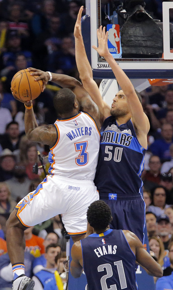 Photo - Oklahoma City's Dion Waiters (3) tries to get a shot off over Dallas' Salah Mejri (50) during the NBA basketball game between the Oklahoma City Thunder and the Dallas Mavericks at Chesapeake Energy Arena on Wednesday, Jan. 13, 2016, in Oklahoma City, Okla.  Photo by Chris Landsberger, The Oklahoman