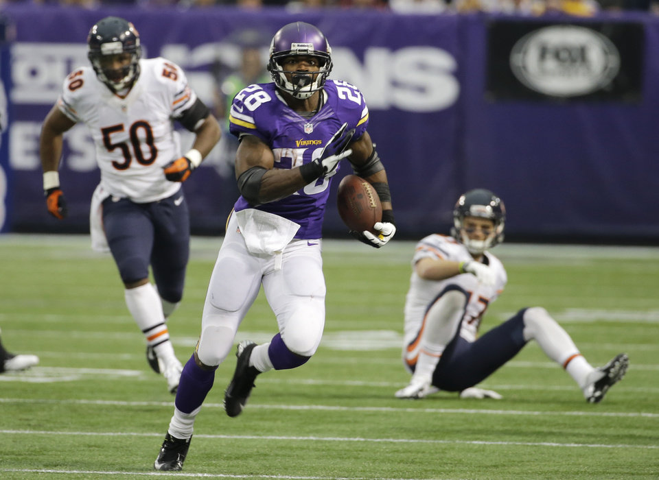 Photo - Minnesota Vikings running back Adrian Peterson, center, runs from Chicago Bears defenders James Anderson, left, and Chris Conte, right, during the first half of an NFL football game on Sunday, Dec. 1, 2013, in Minneapolis. (AP Photo/Ann Heisenfelt)