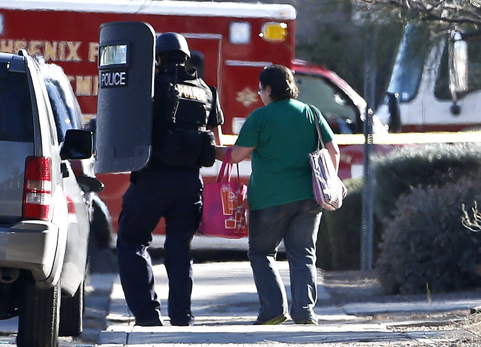 Photo - A member of the Phoenix Police Department SWAT team leads a female neighbor away to safety, as the the SWAT team prepares to enter the home of a suspected gunman who opened fire at a Phoenix office building, wounding three people, one of them critically, and setting off a manhunt that led police to surround his house for several hours before they discovered he wasn't there, Wednesday, Jan. 30, 2013, in Phoenix.  Authorities believe there was only one shooter, but have not identified him or a possible motive for the shooting. They don't believe the midmorning shooting at the complex was a random act. (AP Photo/Ross D. Franklin)