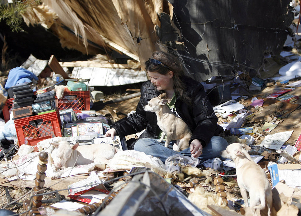 Photo - Christian Clemens and her dog Sierra clean up tornado damage at their home, Thursday, Feb. 12, 2009, in Lone Grove, Okla. PHOTO BY SARAH PHIPPS, THE OKLAHOMAN