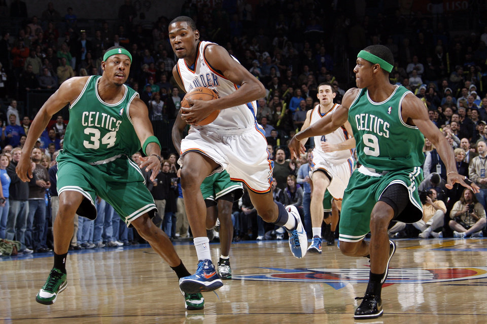 Photo - Oklahoma City's Kevin Durant (35) tries to get past Paul Pierce (34) and Rajon Rondo (9) of Boston in the first half of the NBA basketball game between the Boston Celtics and the Oklahoma City Thunder at the Ford Center in Oklahoma City, Friday, Dec. 4, 2009. Photo by Nate Billings, The Oklahoman ORG XMIT: KOD