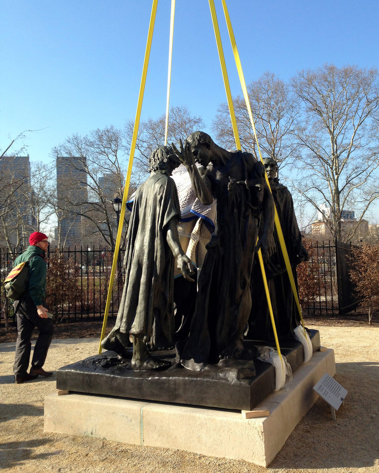 "Auguste Rodin's ""The Burghers of Calais"" is set down with a giant crane Friday, March 22, 2013 outside the Rodin Museum in Philadelphia, which reopened last summer after a three-year renovation inside and out. The sculpture is outdoors in the museum's garden, where it was first installed in 1929. It came indoors in the 1960s because the elements were taking a toll on the 6,000-pound bronze sculpture. Conservators say technological advances allowed them to remove corrosion from the ""The Burghers"" with lasers and chemical compounds. A new coating system will protect the sculpture from future weathering.  (AP Photo/JoAnn Loviglio)"