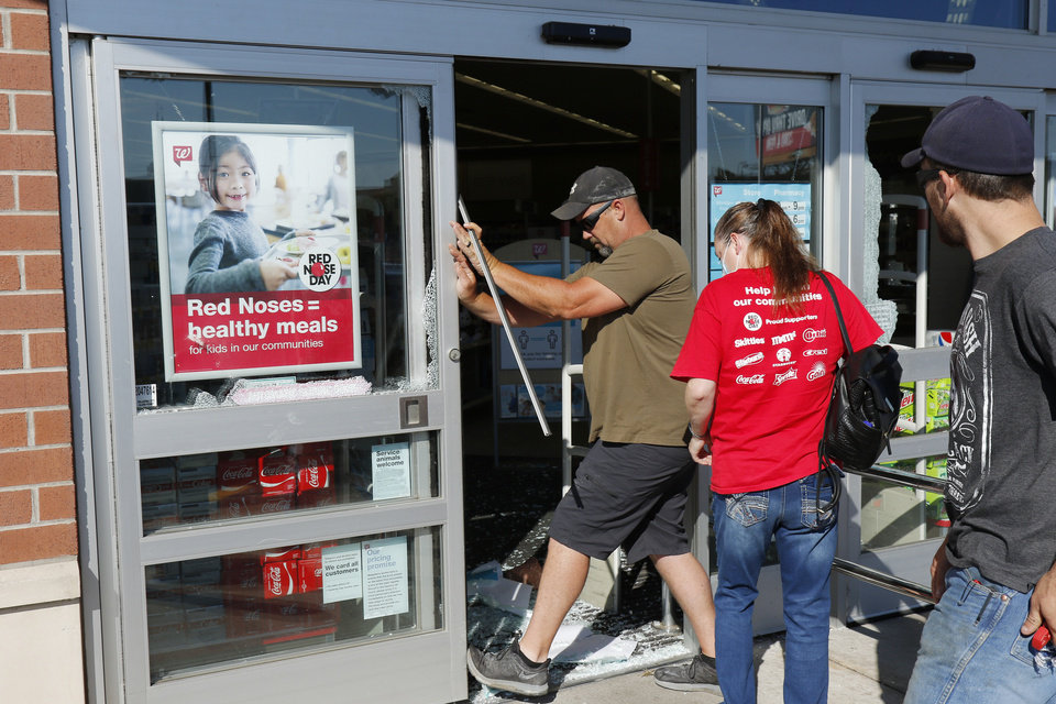 Photo - Chris Clark helps open a damaged door at the Walgreens at NW 23rd and Classen Blvd. Damage from Saturday night protest in downtown Oklahoma City, Sunday, May 31, 2020. [Doug Hoke/The Oklahoman]