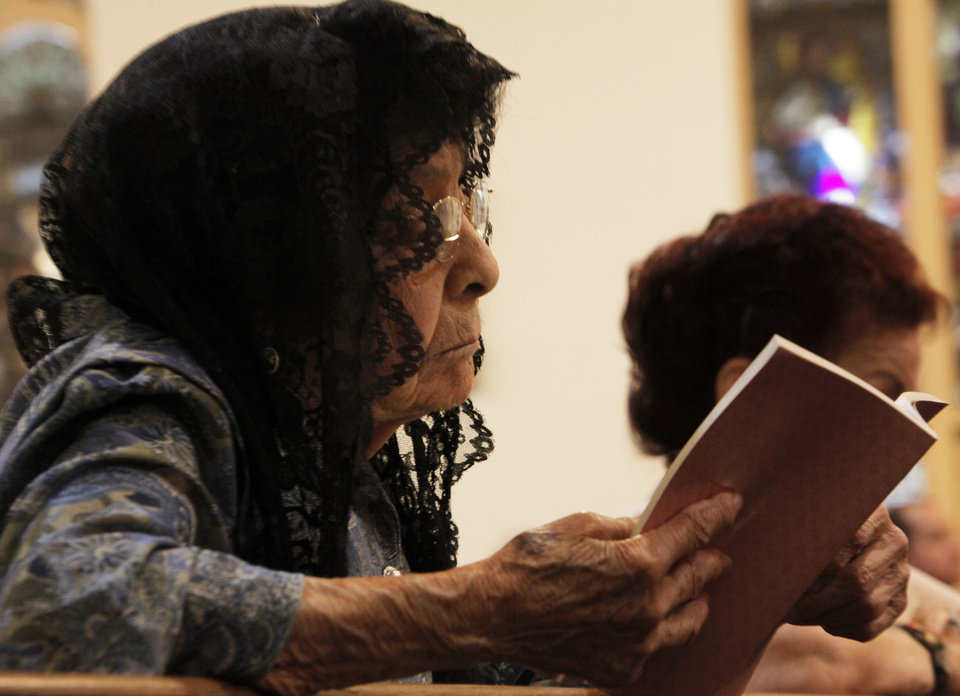 Photo - Margarita Martinez, 94, of Oklahoma City, reads the Bible at Little Flower Church during service on July 21, 2013. Martinez has been a member of the church since 1926. Photo by K.T. KING, The Oklahoman  KT King - KT KING