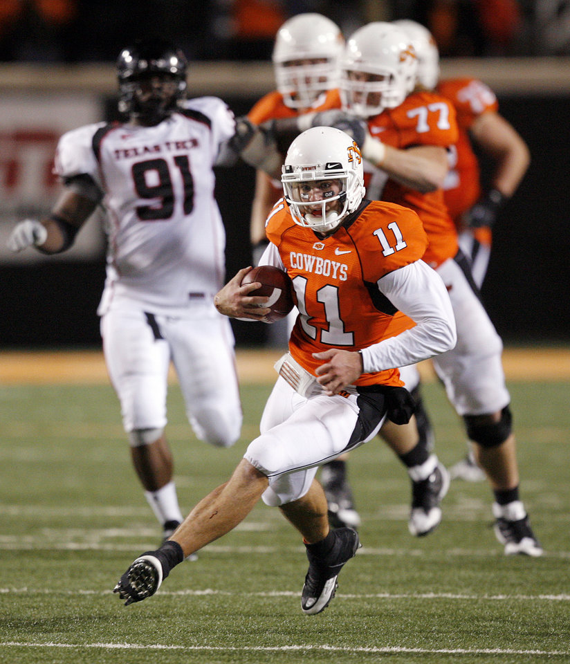Photo - OSU quarterback Zac Robinson (11) carries the ball for 22 yards in the fourth quarter during the college football game between Oklahoma State University (OSU) and Texas Tech University at Boone Pickens Stadium in Stillwater, Okla. Saturday, Nov. 14, 2009. OSU won, 24-17. Photo by Nate Billings, The Oklahoman