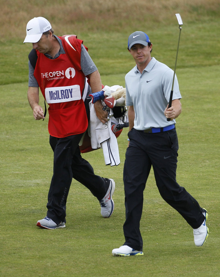 Photo - Rory McIlroy of Northern Ireland acknowledges the crowd as he walks with his caddie JP Fitzgerald up to the 18th green during the third day of the British Open Golf championship at the Royal Liverpool golf club, Hoylake, England, Saturday July 19, 2014. (AP Photo/Peter Morrison)