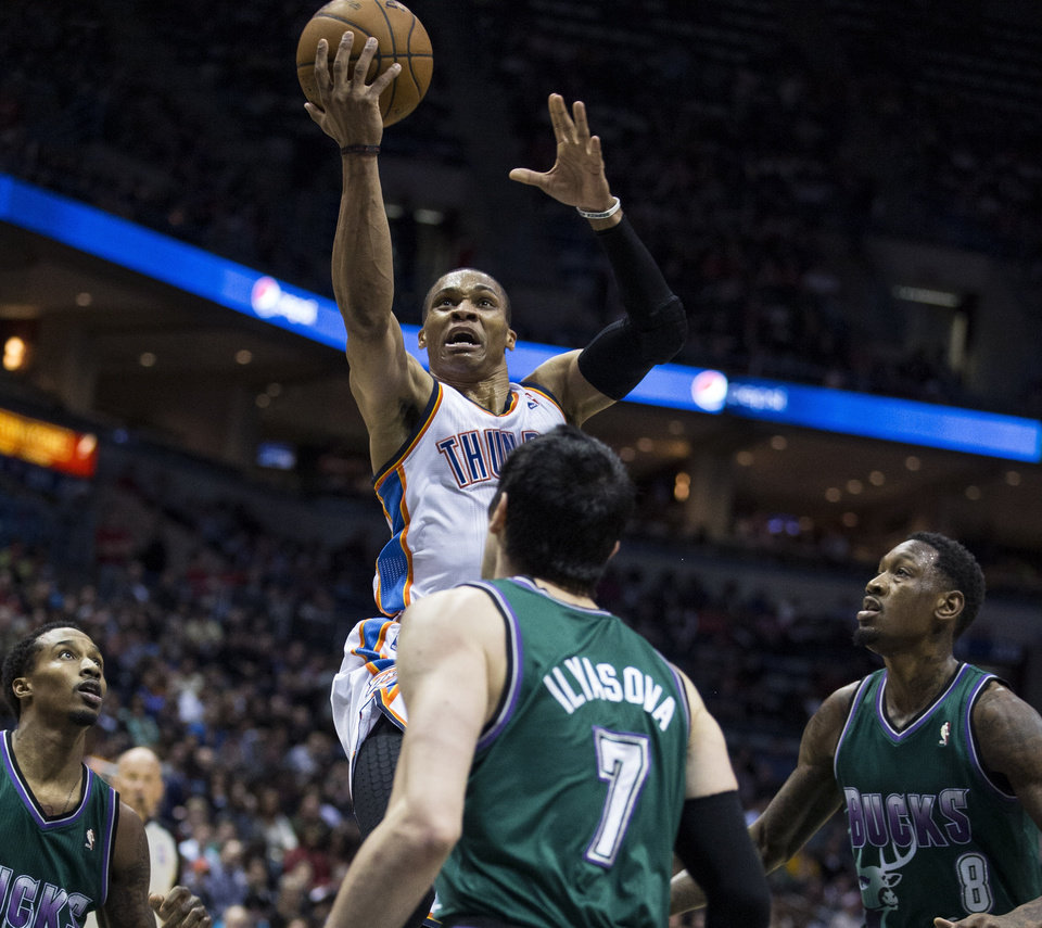 Oklahoma City Thunder\'s Russell Westbrook, top, shoots over Milwaukee Bucks\' Brandon Jennings, left, Ersan Ilyasova, center, and Larry Sanders during the first half of an NBA basketball game on Saturday, March 30, 2013, in Milwaukee. (AP Photo/Tom Lynn)