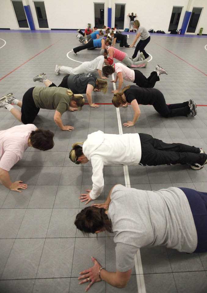 Photo - EXERCISE: Ladies do push-ups during a New Year's Boot Camp at the Holy Trinity Lutheran Church in Edmond, OK, Saturday, Jan. 2, 2010. By Paul Hellstern, The Oklahoman ORG XMIT: KOD