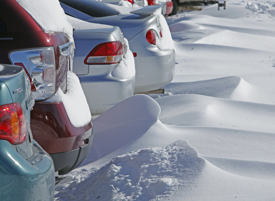 Photo - Student vehicles are surrounded by snow at the University of Oklahoma on Wednesday, February 2, 2011, in Norman, Okla.  Wind and snow from Tuesday's storm created strange snow drifts and cancelled classes.  Photo by Steve Sisney, The Oklahoman