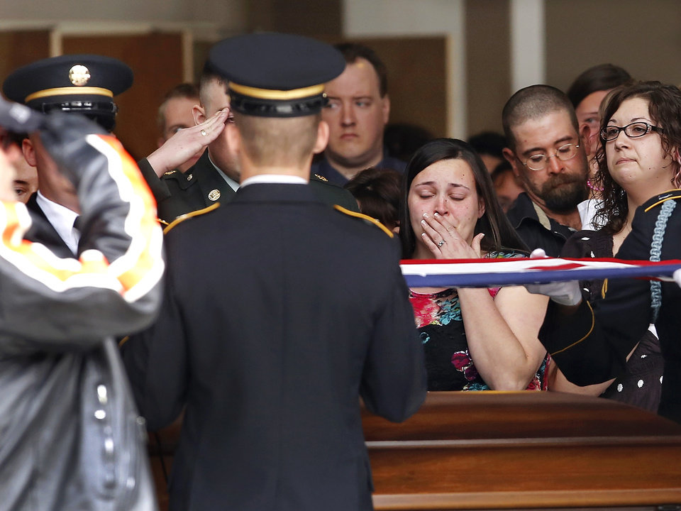 Grief can be seen on the face of Miranda Whipple as military honor guard slowly and precisely fold the American flag that once draped the casket of her brother-in-law, Rex Schad. Schad\'s brother, US Army Spc. Max Whipple is partially shown saluting as the flag is folded. Celebration of Life service for US Army SSgt. Rex L. Schad at LifeChurch.tv in Edmond Thursday afternoon, March 21, 2013. Schad was killed earlier this month while conducting a patrol brief with the Afghanistan National Police. He is a 2005 graduate of Edmond Memorial High School. Photo by Jim Beckel, The Oklahoman