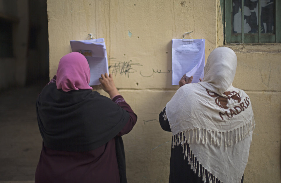 Photo - Women search for their names on a polling list before casting their votes in the country's constitutional referendum in Cairo, Egypt, Tuesday, Jan. 14, 2014. Egyptians have started voting on a draft for their country's new constitution that represents a key milestone in a military-backed roadmap put in place after President Mohammed Morsi was overthrown in a popularly backed coup last July. (AP Photo/Khalil Hamra)