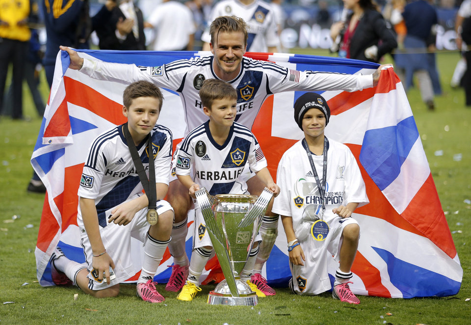 Photo - Los Angeles Galaxy's David Beckham, top center, of England, poses with his sons, from left, Brooklyn, Romeo and Cruz after the Galaxy's 3-1 win in the MLS Cup championship soccer match against the Houston Dynamo in Carson, Calif., Saturday, Dec. 1, 2012. (AP Photo/Jae C. Hong)