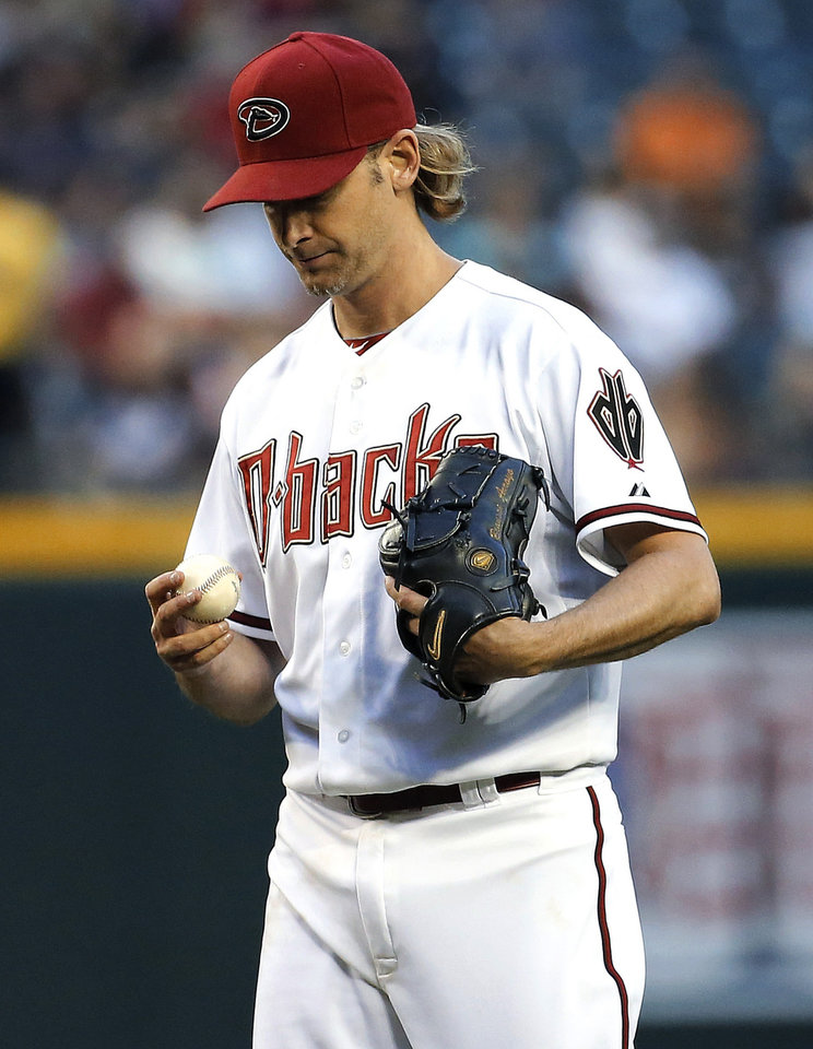 Photo - Arizona Diamondbacks pitcher Bronson Arroyo looks down after giving up a grand slam to the Cincinnati Reds during the second inning of a baseball game, Friday, May 30, 2014, in Phoenix. (AP Photo/Matt York)