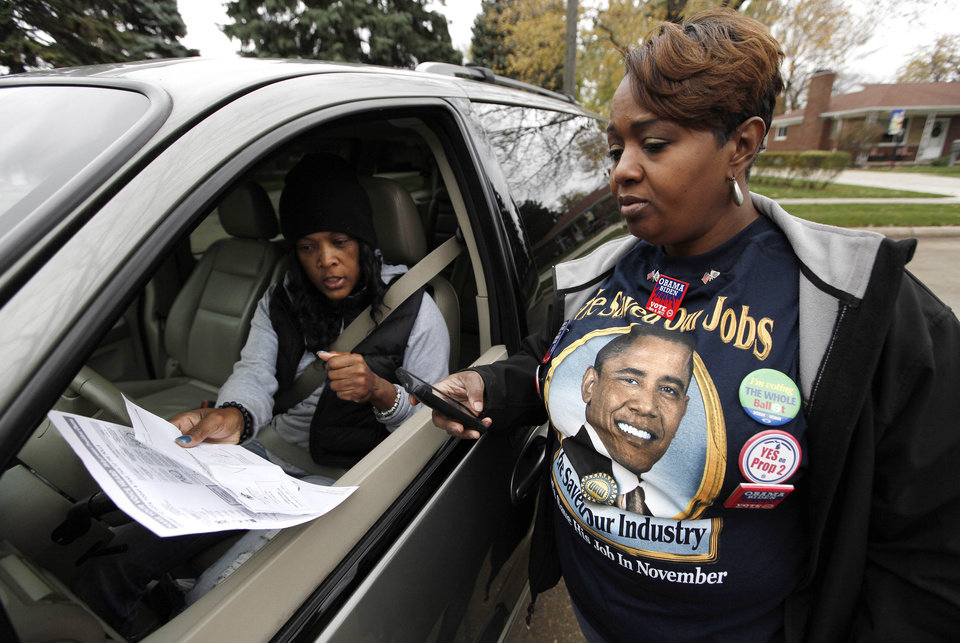 Photo -   United Auto Workers member Keely Bell, right, helps Cecilia Mealy find her polling location, while knocking on doors to remind people to vote on Election Day Tuesday, Nov. 6, 2012 in Warren, Mich. For Bell, 42, this was her first up-close view of a UAW Election Day. She'd been out of work for two-and-a-half years, after losing a long-time office job, when a rebounding Chrysler hired her to a nearby assembly two years ago. (AP Photo/Paul Sancya)