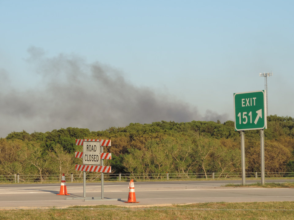 Photo -  Smoke rises Sunday afternoon from the wildfire near Guthrie. Photo by Keilee Painter, For NewsOK.com      -