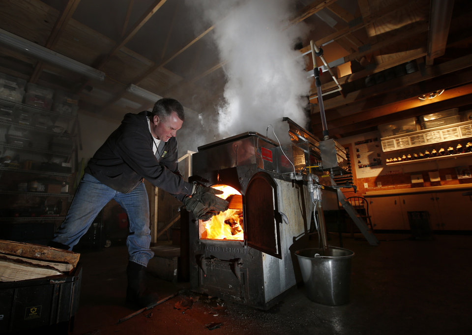 Photo - In this March 13, 2014 photo, Paul Boulanger tosses wood in to fire up the sap evaporator at the Turtle Lane Maple sugar house in North Andover, Mass. It takes about 40 gallons of sap to yield one gallon of syrup. Maple syrup season is finally under way in Massachusetts after getting off to a slow start because of unusually cold weather. (AP Photo/Elise Amendola)