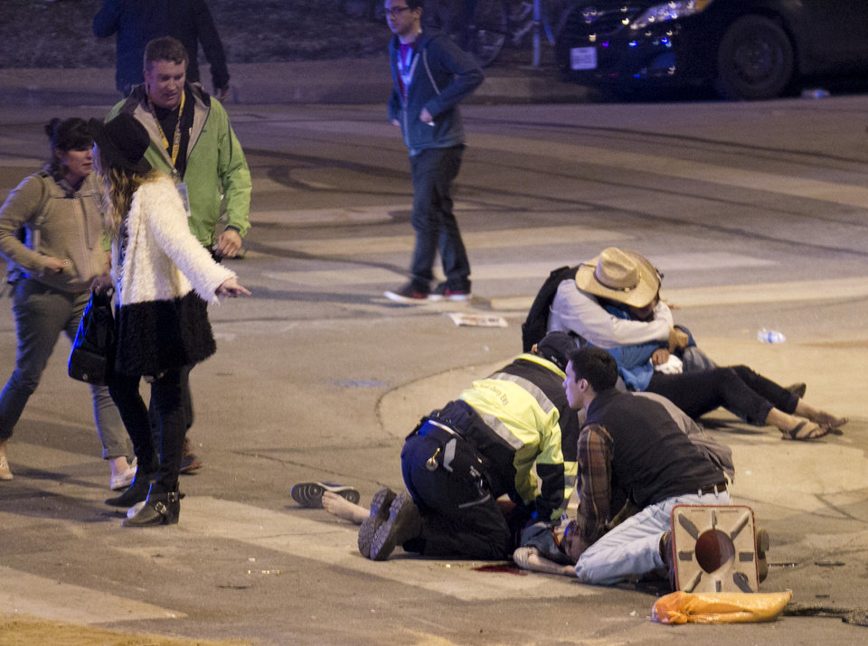 Photo - People perform CPR on a woman after she was struck by a vehicle on Red River Street in downtown Austin, Texas, at SXSW on Wednesday March 12, 2014. Police say a man and woman have been killed after a suspected drunken driver fleeing from arrest crashed through barricades set up for the South By Southwest festival and struck the pair and others on a crowded street. (AP Photo/Austin American-Statesman, Jay Janner)
