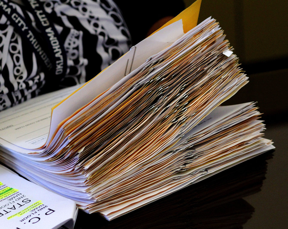 A court clerk holds a thick stack of paperwork representing a large number of jailed inmates set to appear Tuesday before Special Judge Russell Hall during a video arraignment in Hall's chamber. Photo by Jim Beckel, The Oklahoman