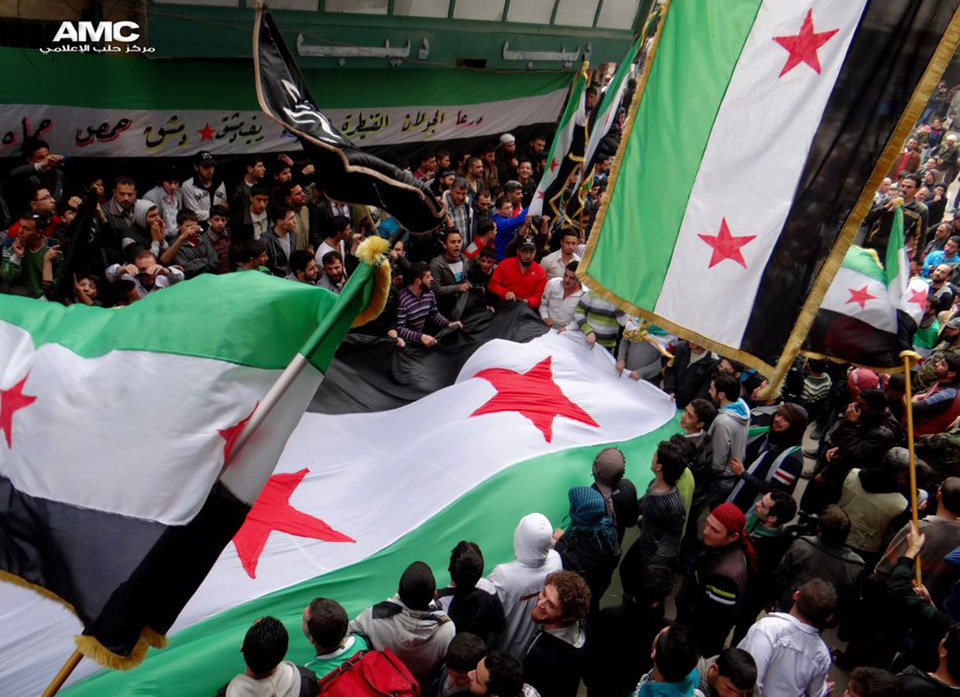 Photo - In this citizen journalism image provided by Aleppo Media Center AMC which has been authenticated based on its contents and other AP reporting, anti-Syrian regime protesters, wave the Syrian revolutionary flags during a protest to mark the second anniversary of the their uprising, in Aleppo, Syria, Friday March 15, 2013. The chief of Syria's main, western-backed rebel group marked the second anniversary of the start of the uprising against President Bashar Assad on Friday by pledging to fight until the