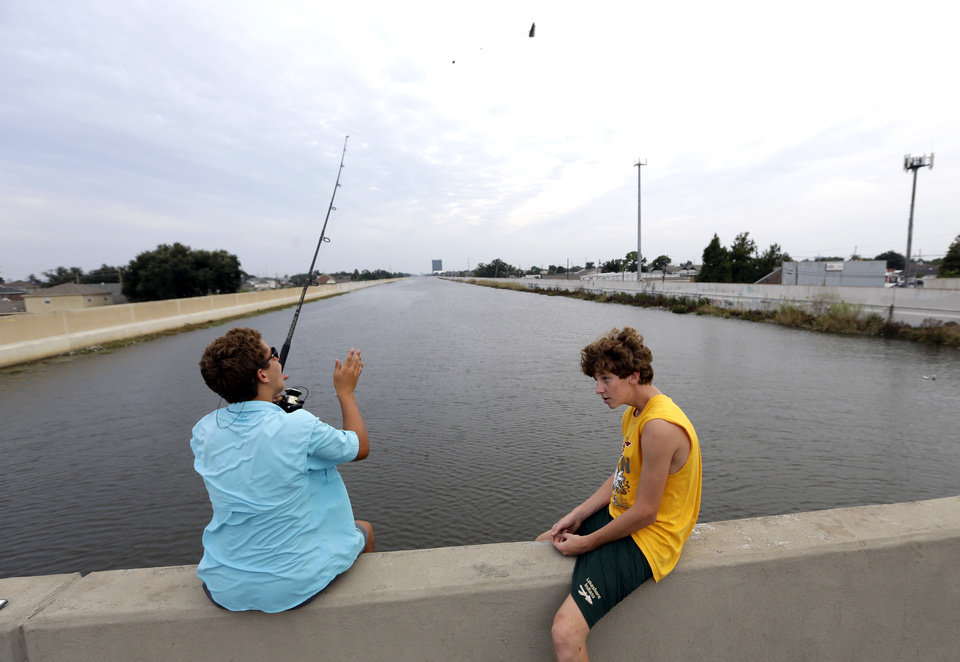 Photo -   Dylan Lacoste, 14, left, and Joey Taylor, 15, fish from the 17th Street Canal bridge Monday, Aug. 27, 2012, in New Orleans. Seven years ago this week, Hurricane Katrina hit New Orleans. Tropical Storm Isaac is churning it's way across the Gulf of Mexico and could make landfall near New Orleans later this week. (AP Photo/David J. Phillip)