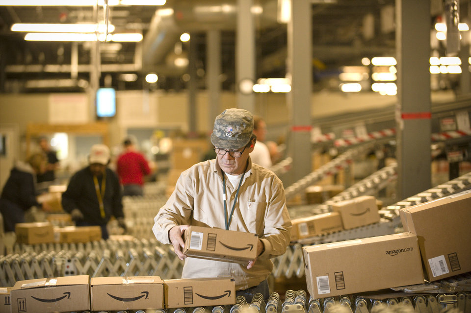 Photo -   FILE - In this Monday, Dec., 1, 2008, file photo, an Amazon.com employee grabs boxes off the conveyor belt to load in a truck at their Fernley, Nev., warehouse. Cyber Monday, coined in 2005 by a shopping trade group that noticed a spike in online sales on the Monday after Thanksgiving when people returned to their work computers, is the next in a line of days that stores are counting on to jumpstart the holiday shopping season. This year it is expected to be the biggest online shopping day of the year for the third year in a row. (AP Photo/Scott Sady)