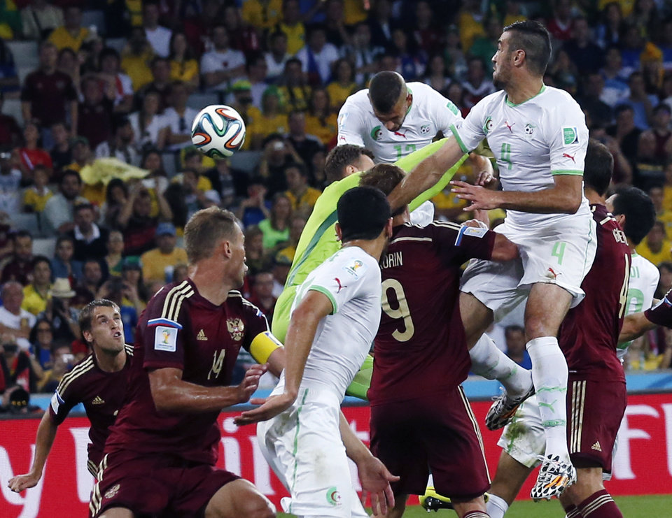 Photo - Algeria's Islam Slimani heads the ball to score during the group H World Cup soccer match between Algeria and Russia at the Arena da Baixada in Curitiba, Brazil, Thursday, June 26, 2014. (AP Photo/Jon Super)