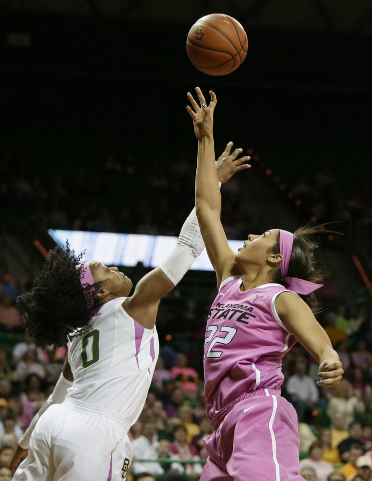 Photo - Baylor's Odyssey Sims (0) and Oklahoma State's Brittney Martin (22) compete for a rebound in the first half of an NCAA college basketball game on Sunday, Feb. 9, 2014, in Waco, Texas. Both teams wore uniforms accented with pink for breast cancer awareness. (AP Photo/Tony Gutierrez)