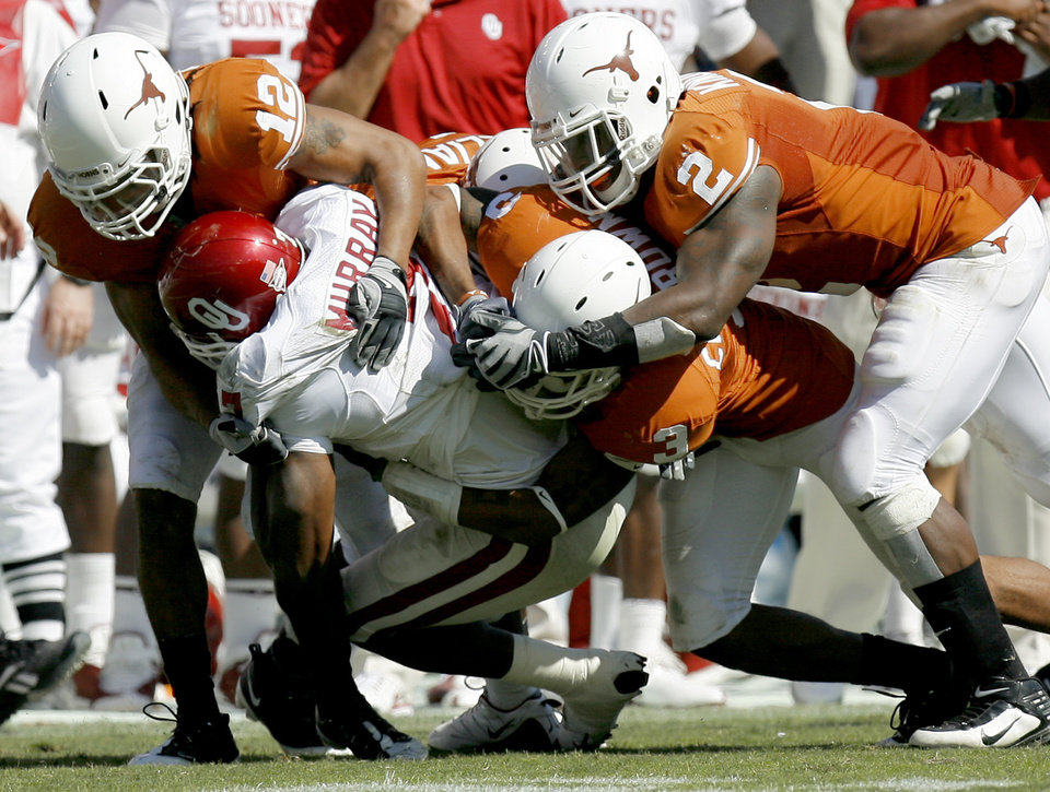 Photo - OU's DeMarco Murray is brought down by Earl Thomas, left, Curtis Brown, and Sergio Kindle of Texas during the Red River Rivalry college football game between the University of Oklahoma Sooners (OU) and the University of Texas Longhorns (UT) at the Cotton Bowl in Dallas, Texas, Saturday, Oct. 17, 2009. Photo by Bryan Terry, The Oklahoman