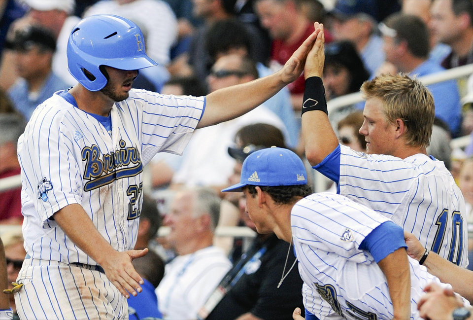 UCLA\'s Pat Gallagher, left, is greeted by teammates including Pat Valaika (10) after scoring against North Carolina on a single by Cody Regis in the second inning of an NCAA College World Series baseball game in Omaha, Neb., Friday, June 21, 2013. (AP Photo/Eric Francis)