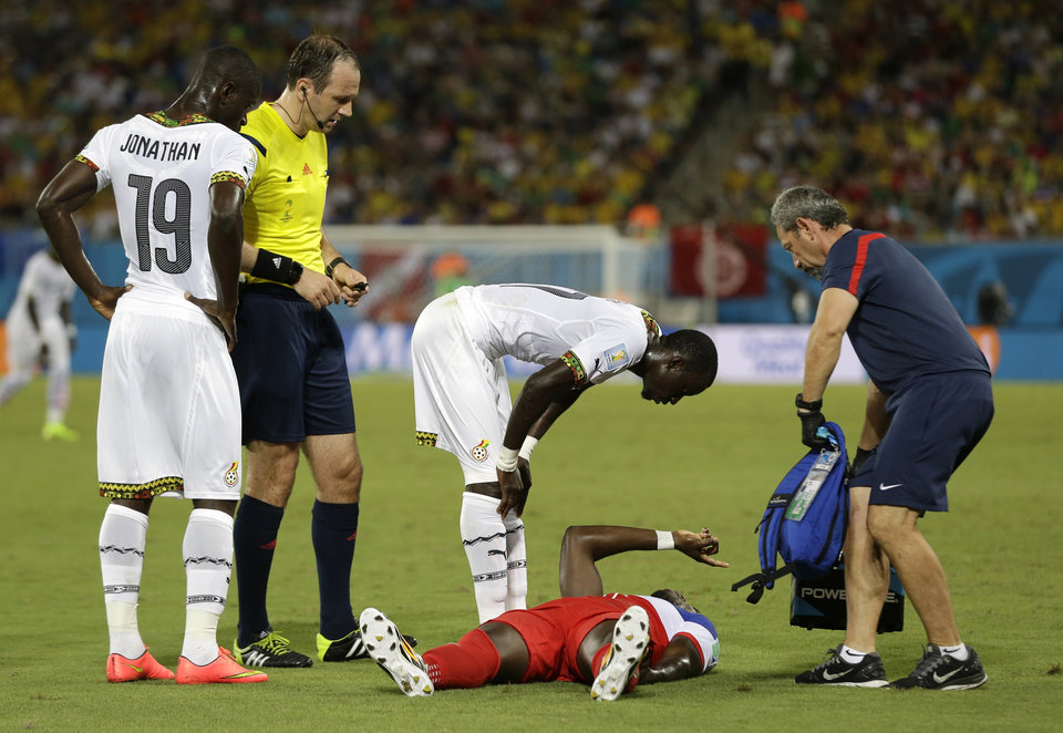 Photo - United States' Jozy Altidore gestures as he lies on the pitch after pulling up injured, as referee Jonas Eriksson of Sweden, looks on as a United States team trainer arrives to help during the group G World Cup soccer match between Ghana and the United States at the Arena das Dunas in Natal, Brazil, Monday, June 16, 2014. (AP Photo/Ricardo Mazalan)