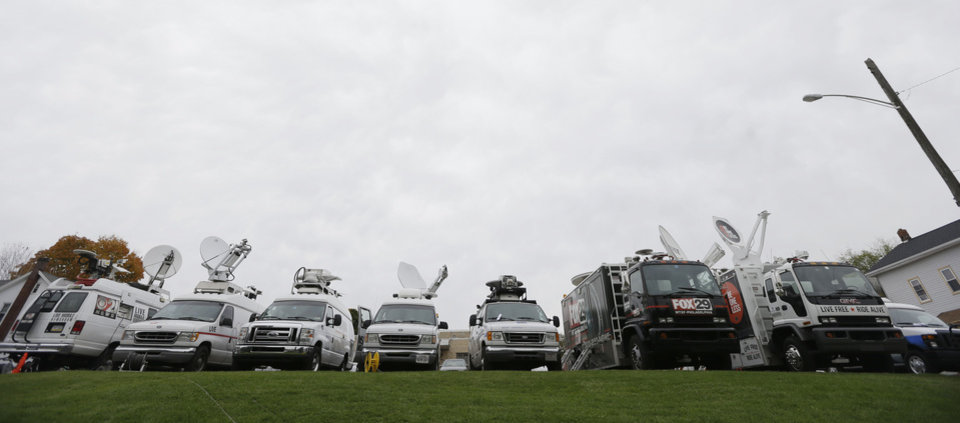 Photo -   News trucks fill a parking lot near the Centre County Courthouse Monday, Oct. 8, 2012, in Bellefonte, Pa. Former Penn State University assistant football coach Jerry Sandusky is scheduled to be sentenced Tuesday for sexually abusing 10 boys in a scandal that rocked the university and brought down coach Joe Paterno. (AP Photo/Matt Rourke)