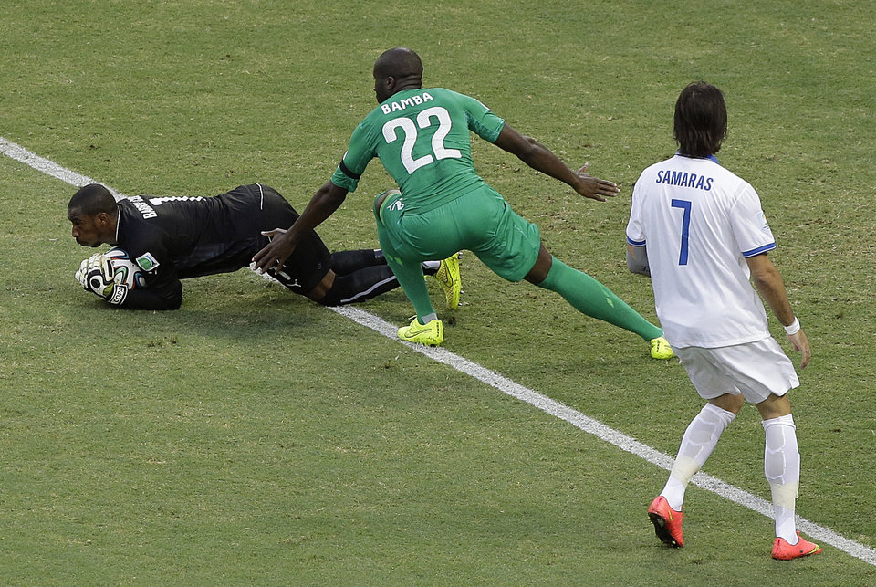Photo - Ivory Coast's goalkeeper Boubacar Barry, left, makes a save as teammate Sol Bamba (22) and Greece's Giorgos Samaras look on during the group C World Cup soccer match between Greece and Ivory Coast at the Arena Castelao in Fortaleza, Brazil, Tuesday, June 24, 2014. (AP Photo/Sergei Grits)