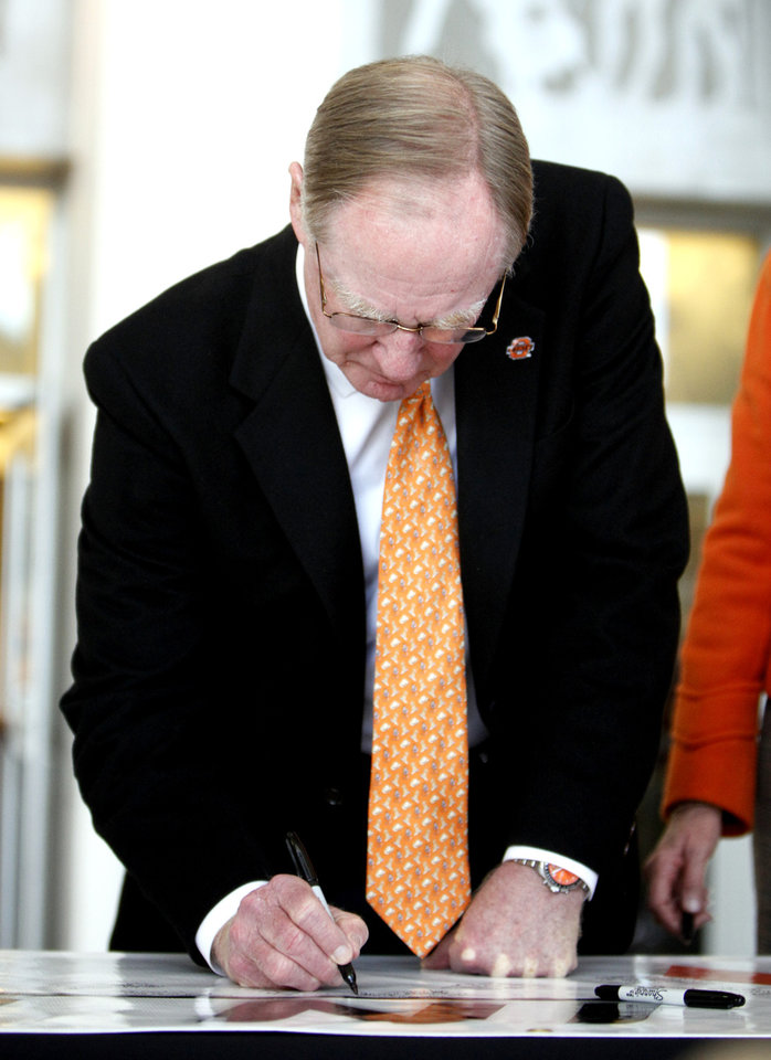 Oklahoma State president Burns Hargis signs a memorial banner for women's basketball coach Kurt Budke, assistant coach Miranda Serna at Gallagher- Iba Arena in Stillwater, Okla.,  Friday, Nov. 18, 2011.  Photo by Sarah Phipps, The Oklahoman
