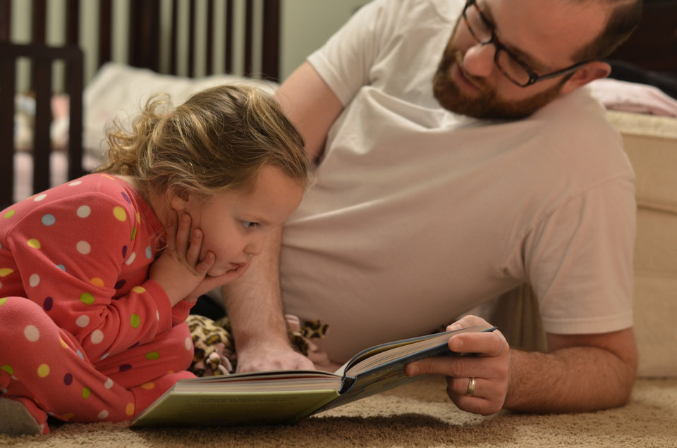 Isabella and Michael Mitchell, of Edmond, look at a book together.  Photo provided <strong></strong>