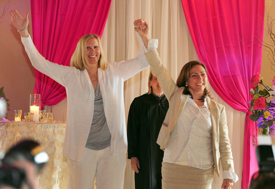 Photo - Julie Engbloom, left, and Laurie Brown, right, get married by Judge Beth A. Allen at the Melody Ballroom, Monday, May 19, 2014,  in Portland, Ore. Federal Judge Michael McShane released an opinion on Oregon's Marriage Equality lawsuit that grants gay and lesbian couples the freedom to marry in Oregon. (AP Photo/Steve Dykes)