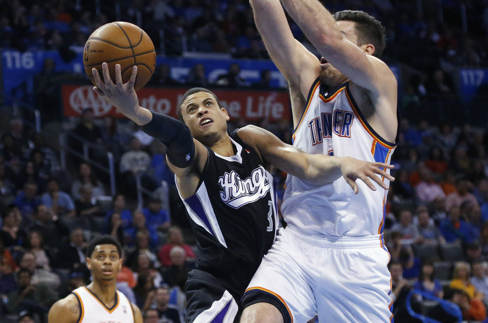 Photo - Sacramento Kings guard Ray McCallum (3) shoots in front of Oklahoma City Thunder forward Nick Collison during the second quarter of an NBA basketball game in Oklahoma City, Friday, March 28, 2014. (AP Photo/Sue Ogrocki)