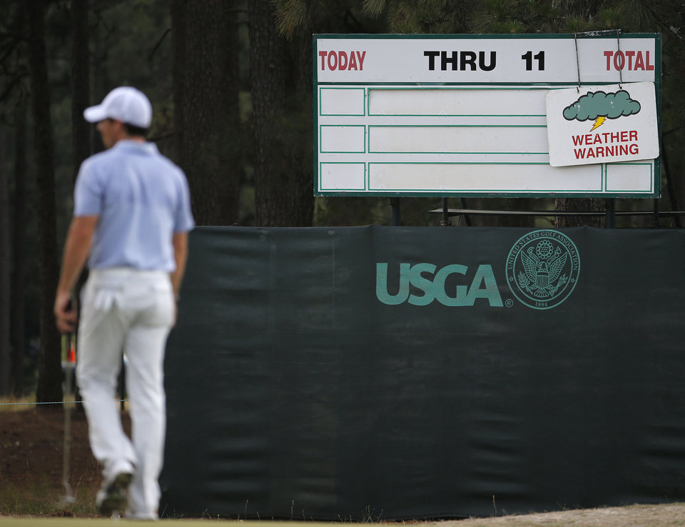 Photo - Rory McIlroy, of Northern Ireland, leaves the course after practice was suspended due to weather at the U.S. Open golf tournament in Pinehurst, N.C., Wednesday, June 11, 2014. The tournament starts Thursday. (AP Photo/Matt York)
