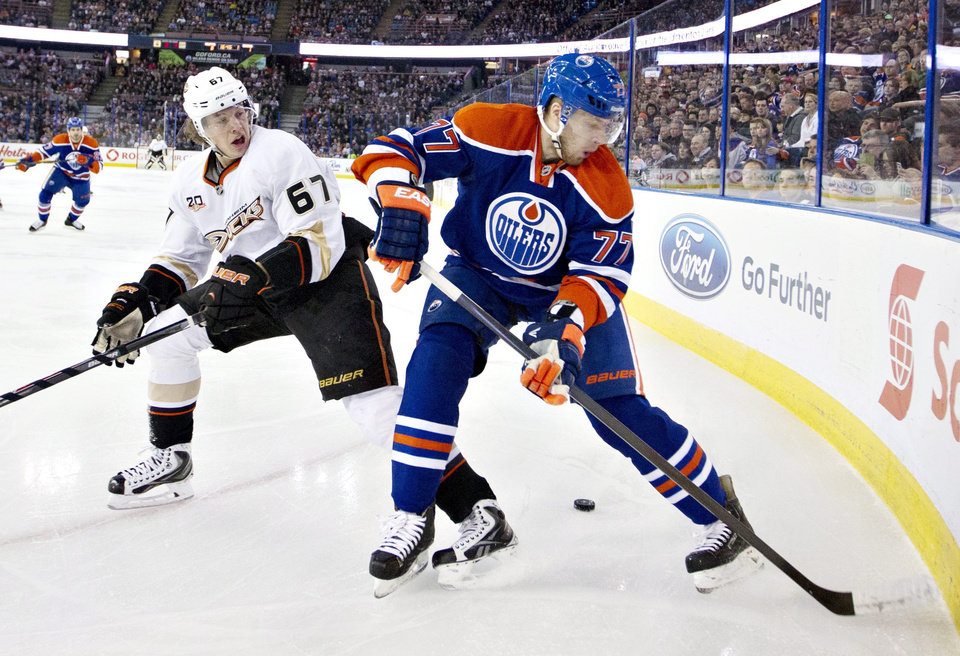 Photo - Anaheim Ducks' Rickard Rakell (67) battles in the corner with Edmonton Oilers' Anton Belov (77) during first-period NHL hockey game action in Edmonton, Alberta, Friday, March 28, 2014. (AP Photo/The Canadian Press, Jason Franson)