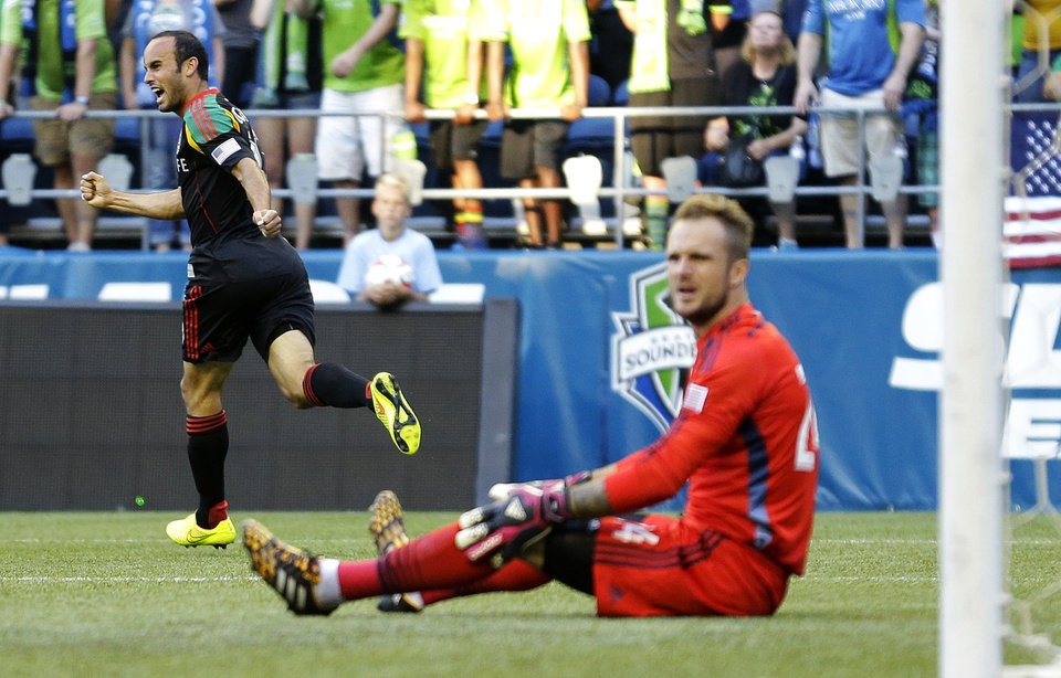 Photo - Los Angeles Galaxy midfielder Landon Donovan, left, celebrates his goal against Seattle Sounders goalkeeper Stefan Frei, right, in the first half of an MLS soccer match, Monday, July 28, 2014, in Seattle. (AP Photo/Ted S. Warren)