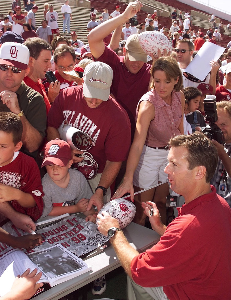 Photo - OU football media day 1999. Bob Stoops signs stuff for fans.