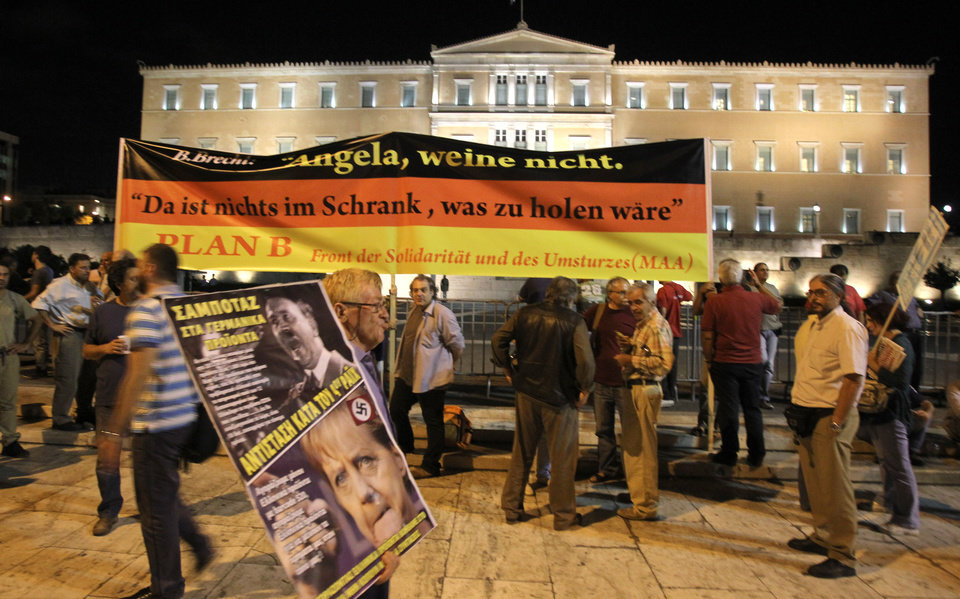 Protestors holding banners protest outside the Greek Parliament in Athens Oct. 8, 2012 during an union anti-austerity rally a day before the visit by German Chancellor Angela Merkel. The authorities are keen to prevent embarrassing riots. More than 7,000 police will be on security duty in the capital from early Tuesday, while public gatherings will be banned in much of the city center and on a 100-meter (yard) radius from the route her motorcade will follow. The ban will not affect the main protests, but will prevent demonstrators from reaching the German embassy, where a populist right wing party was planning a protest. Banners read