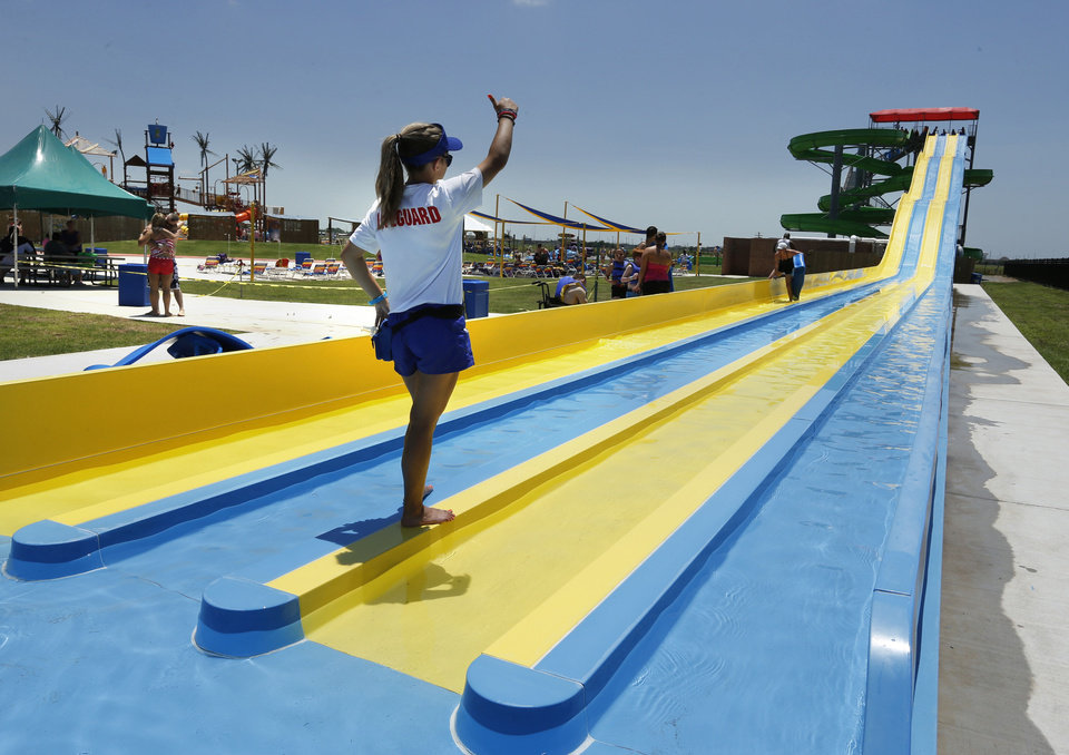 Lifeguard Megan Sidle gives the thumbs-up to start the next group on a giant water slide as people enjoy Andy Alligator's Fun Park. <strong>STEVE SISNEY - THE OKLAHOMAN</strong>