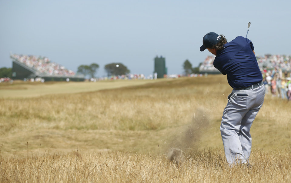 Photo - Phil Mickelson of the United States plays a shot on the 5th hole during the third round of the British Open Golf Championship at Muirfield, Scotland, Saturday July 20, 2013. (AP Photo/Peter Morrison)