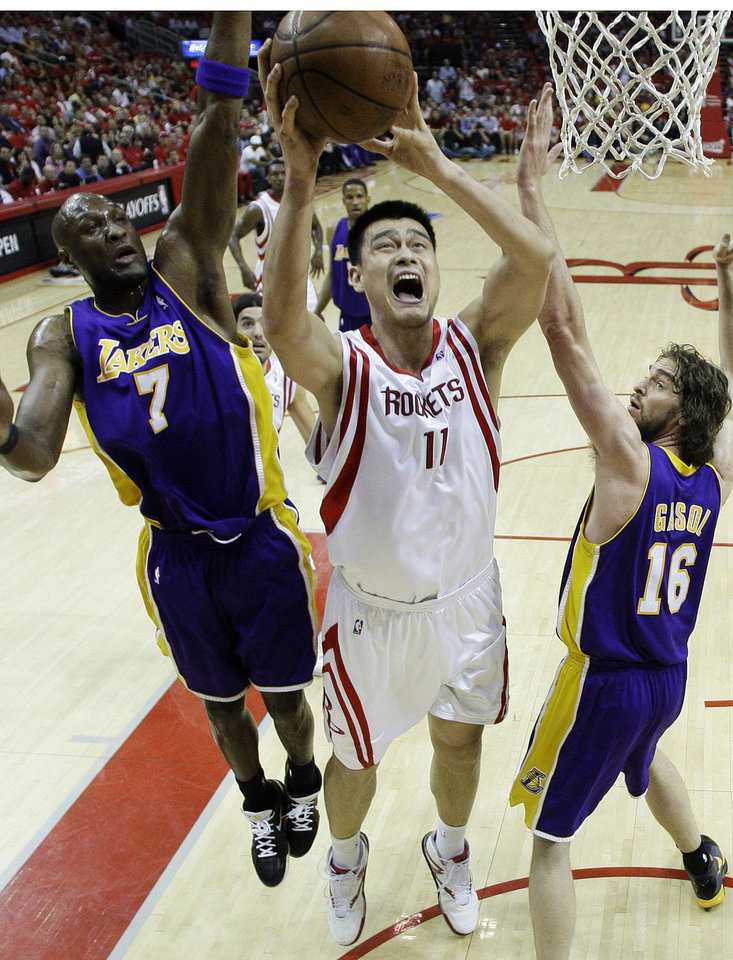 Photo - FILE - In this May 8, 2009, file photo, Houston Rockets center Yao Ming (11), of China, shoots as Los Angeles Lakers forward Pau Gasol (16), of Spain, and forward Lamar Odom (7) defend during the second quarter of Game 3 of a second-round Western Conference NBA playoff basketball game in Houston. Ming has called a possible move to Cleveland an